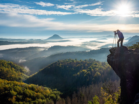 Man making photos of mountains during autumn. Nature photographer with camera in morning mountains