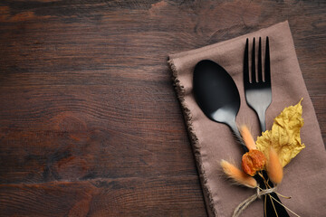 Seasonal table setting on wooden background, space for text. Cutlery with autumn decorations, top view