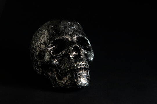 human silver skull on black background