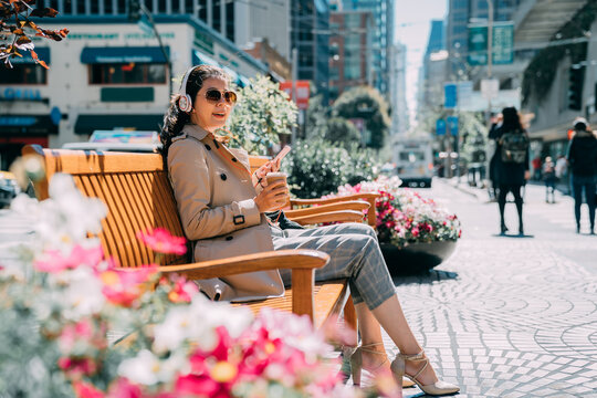 Happy pleased young asian woman chatting on mobile phone while listening music on headphones. smiling pretty female looks aside relaxing on bench with flowers in busy city street on sunshine day.