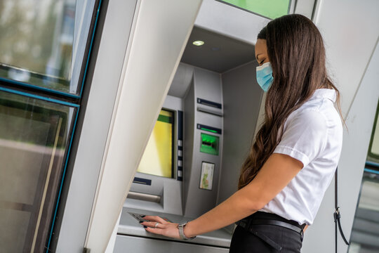 Businesswoman with protective mask is using ATM machine to withdraw cash. Covid-19 virus pandemic concept.