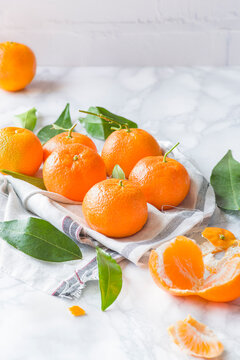 Group of fruits with different names: Tangerine, mandarine or clementine on white marble background..