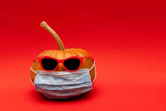 Pumpkin with red sunglasses and face protective medical mask, autumn concept in modern world with coronavirus, red background, copyspace..