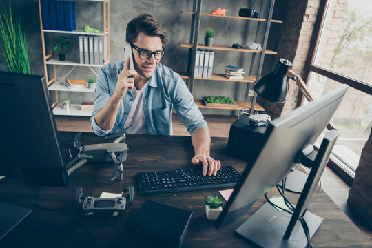 Portrait of his he nice attractive cheerful guy geek expert consulting client on phone monitoring remote network web game dev at modern industrial home office workplace workstation