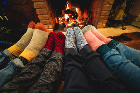 Legs view of happy family lying down next fireplace wearing warm wool socks at home - Winter, Christmas holiday, love and cozy concept - Main focus on right woman feet