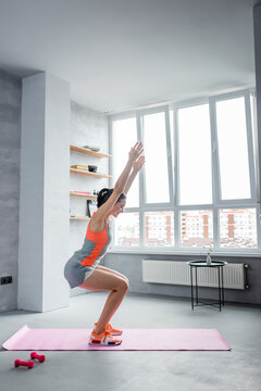 Side view of sportswoman squatting with hands in air on fitness mat at home