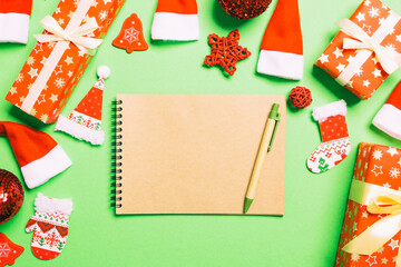 Wall Mural - Top view of notebook on green background made of Christmas decorations. New Year time concept