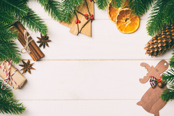 Wall Mural - Top view of fir tree branches and festive decorative toys on wooden background. New Year time concept with empty space for your design