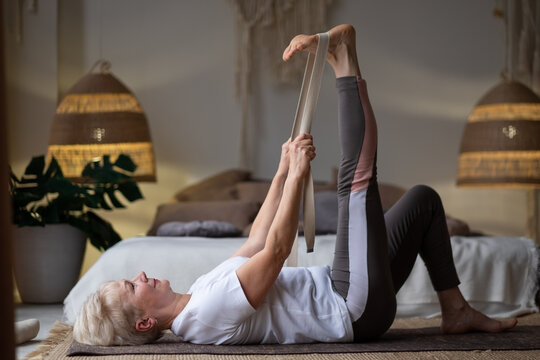 woman working out, warming up using yogic belt, lying in yoga Supta Padangushthasana, One Leg Lift exercise