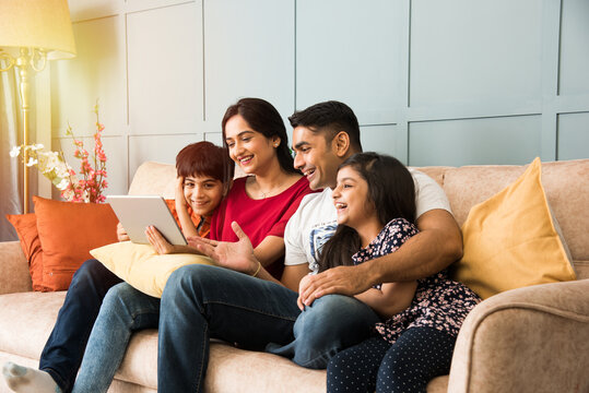 Indian family using smartphone, laptop or tablet, watching movie, surfing internet, sitting on sofa