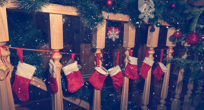 Christmas socks hanging on wooden stairs near fur tree with christmas toys, snowing, christmas and new year dreaming concept.