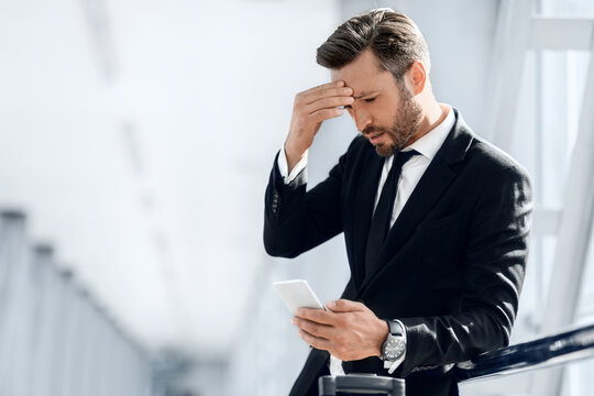Tired businessman standing by window in airport, using phone
