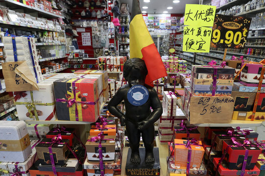 A replica of Brussels' iconic Manneken Pis statue is seen with a sign asking people to wear protective face masks at a chocolate shop, as the spread of the coronavirus disease (COVID-19) continues, in Brussels