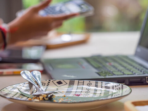 Closeup of blank ceramic plate with blurry notebook, woman 's hand and mobile phone background in house, cafe or office for working or studying from home concept.