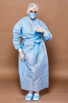 Portrait of a doctor's girl on a peach background in a protective suit