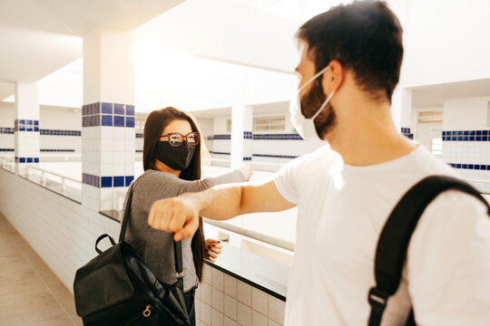 COVID-19: back to school. College students wearing face masks greet with elbows