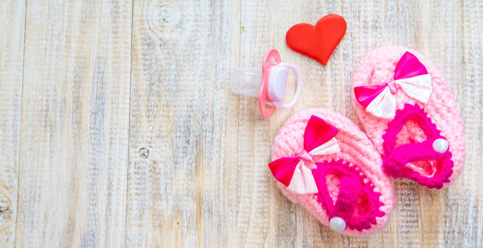 Baby booties and heart on a light background. Selective focus.