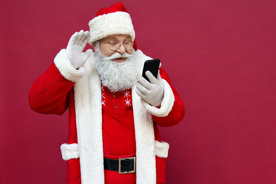 Happy old bearded Santa Claus wearing costume waving hand holding cell phone using mobile app video calling greeting on Merry Christmas on smartphone in virtual online chat isolated on red background.