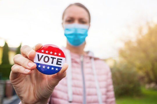 Woman with face mask showing Vote button at american elections outside.