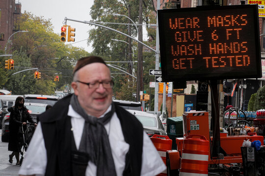 A sign reminds people to wear masks, give 6 ft., wash hands and get tested, during the outbreak of the coronavirus disease (COVID-19) in the Borough Park section of Brooklyn