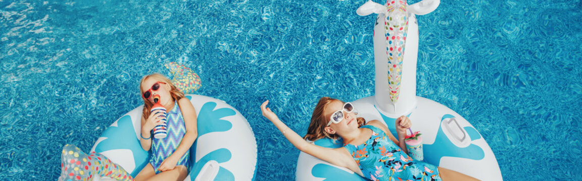 Girls sisters friends with drinks lying on inflatable rings unicorns. Kids children siblings in sunglasses having fun in swimming pool. Summer outdoors water activity for kids. Web banner header.