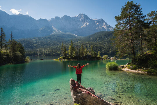 Girl in red jacket standing on a rock and spreading arms, watching a beautiful view over lake Eibsee in the Bavarian Alps. Famous touristic destination.