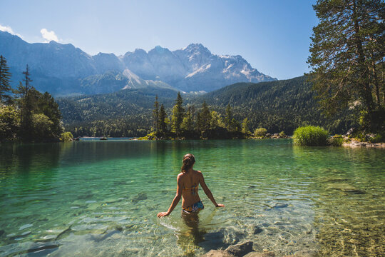 Girl in swimming suite with the back at the camera swimming in a beautiful mountain lake, in the Bavarian Alps