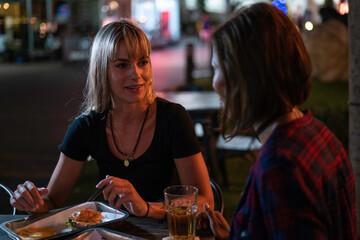 Girlfriends eating burgers in a street restaurant at night Fotomurales