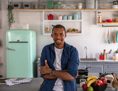 Portrait of a black man sitting on kitchen counter
