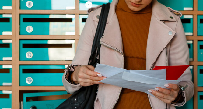 Woman attentively reading mail leaning on mailboxes