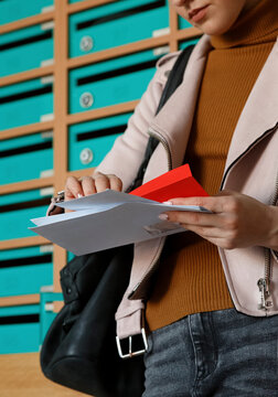 Woman thoughtfully opening envelop leaning on mailboxes