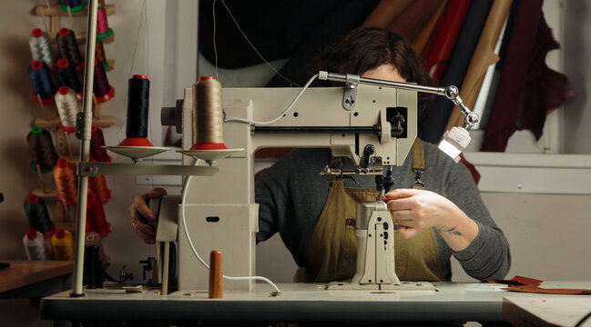 Skilled tailor working in workshop with equipment and sewing