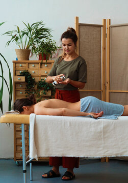 Masseuse with oil preparing for massage