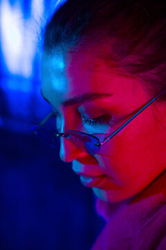 Young woman in eyeglasses in neon light
