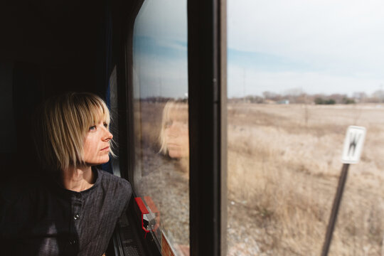 Young Woman Looking Out The Window Traveling On A Train