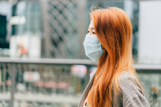 Young business woman wearing medical protective mask on the street