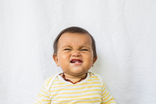 A cute baby grins showing 2 bottom teeth.