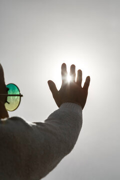 Anonymous man with outstretched hand against sun