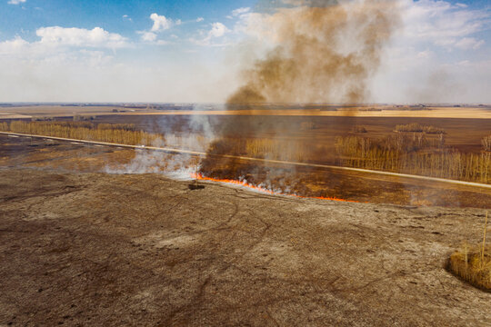 Dangerous fire with gray and brown smoke in countryside in daytime