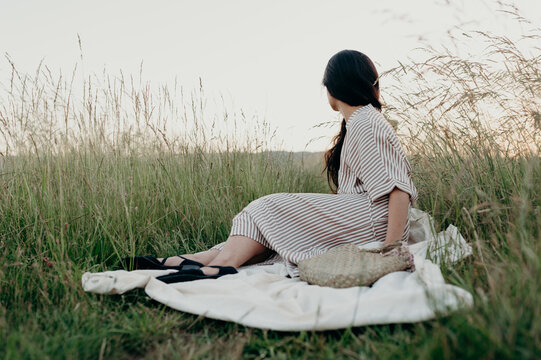 Brunette Filipino woman sitting in a grassy field on a blanket at sunset wearing a tan striped belted dress