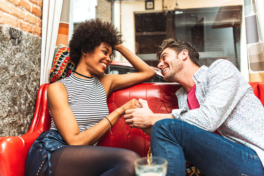 Romantic couple holding hands while looking at each other on sofa in cafe