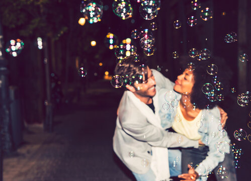 Close-up of bubbles with couple dancing on street in background at night