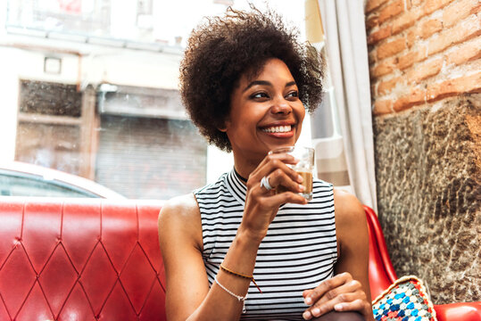 Close-up of smiling woman with curly hair drinking coffee while sitting on sofa in cafe
