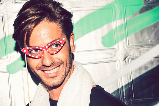 Close-up of smiling man holding eyeglasses prop looking away against wall at night