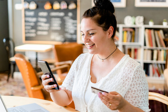 Close-up of smiling young woman holding credit card using smart phone in coffee shop