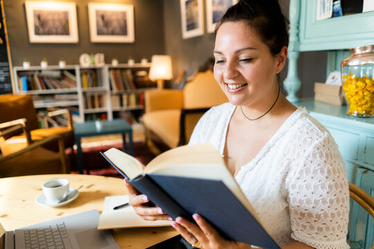 Smiling voluptuous woman reading book while sitting at table in restaurant