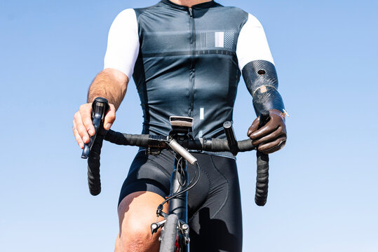 Close-up of male amputee athlete with artificial hand riding bicycle against clear blue sky
