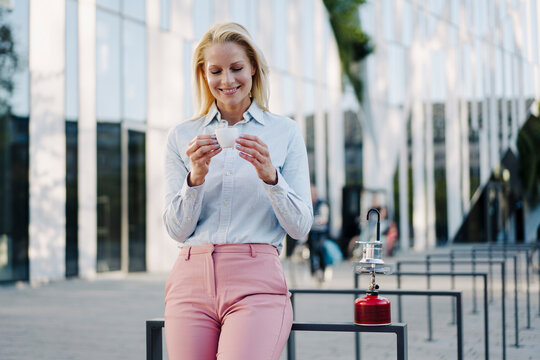 Smiling beautiful blond businesswoman holding coffee cup while leaning by camping stove in financial district