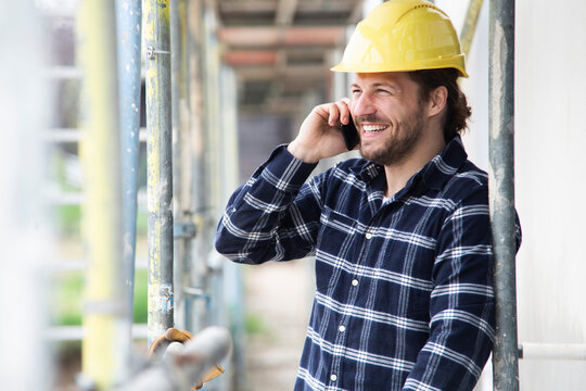 Construction worker talking over smart phone while standing by scaffold at construction site