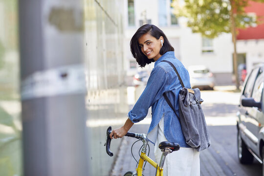 Smiling female commuter with backpack holding bicycle while standing in city